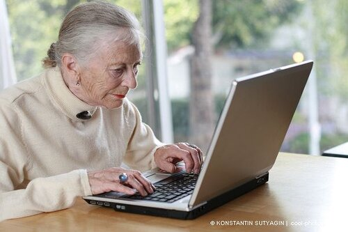 Elderly lady typing on laptop. Shallow DOF. by Konstantin Sutyagin.
